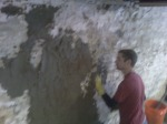 Coating being applied to basement wall for waterproofing